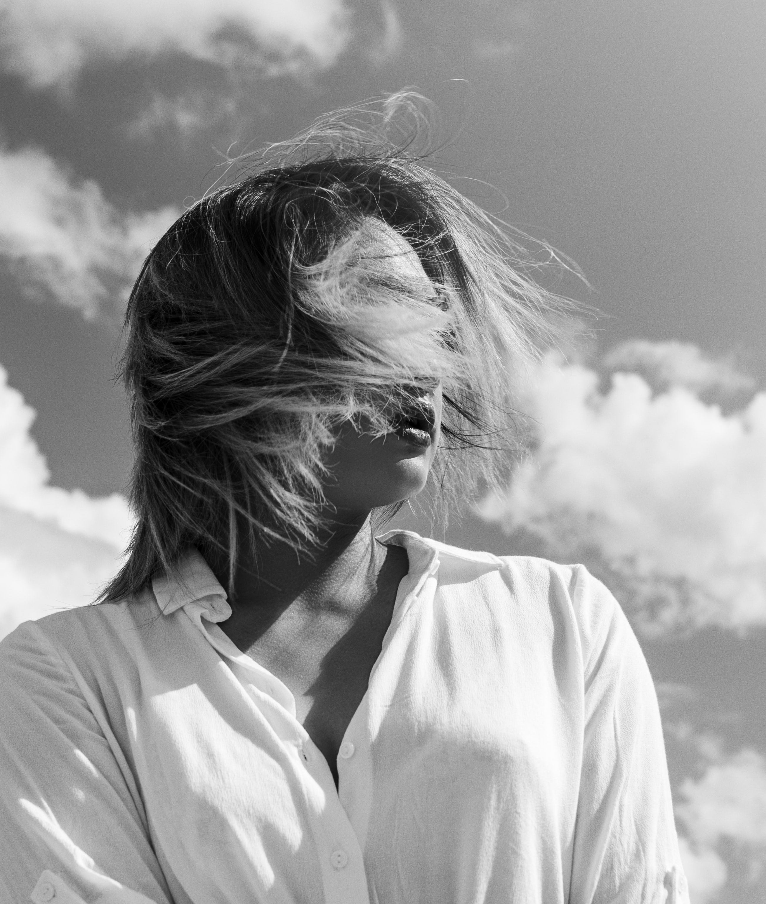 graysale photography of woman wearing collared top with face covered with wind-blown hair during daytime