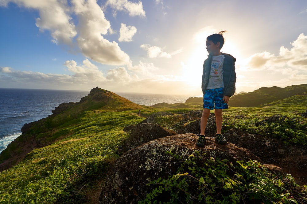 boy standing on rock overlooking sea