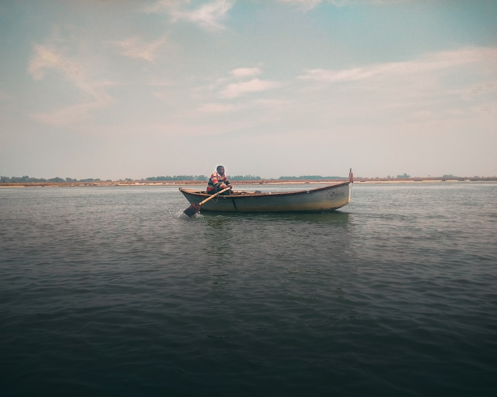 man in boat on a calm water