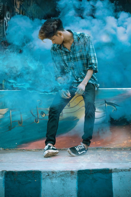man sitting on concrete ledge with blue smoke effect