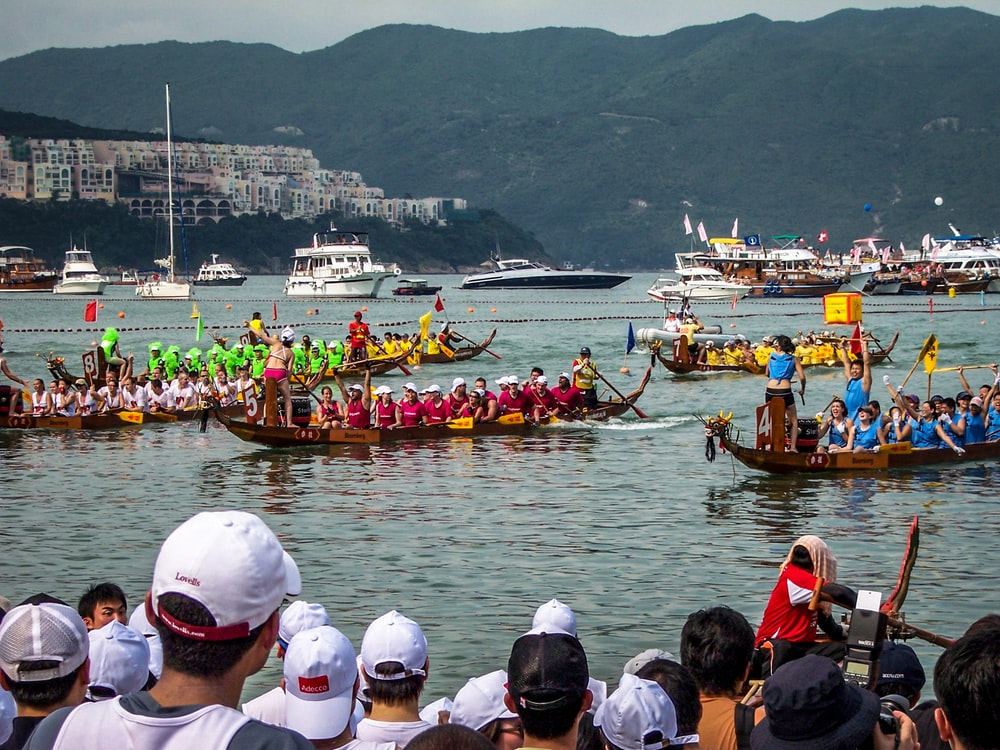 people watching dragon boat competition during daytime