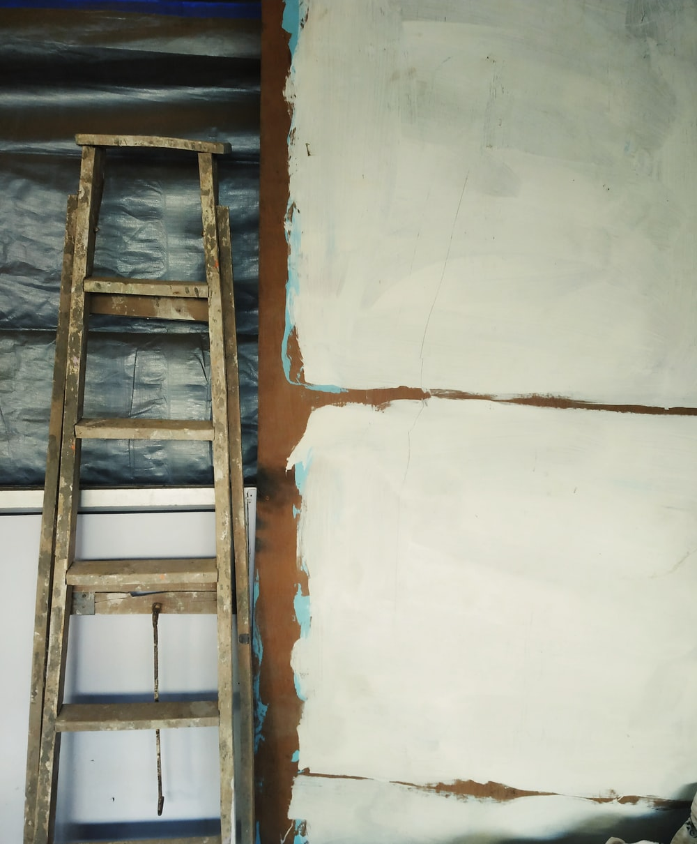gray wooden ladder leaned on white cabinet