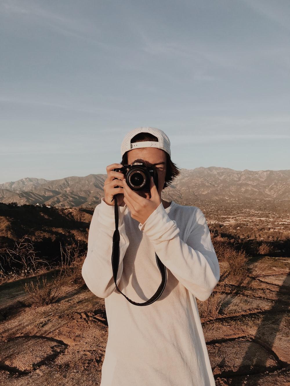 man holding camera standing near mountain ranges
