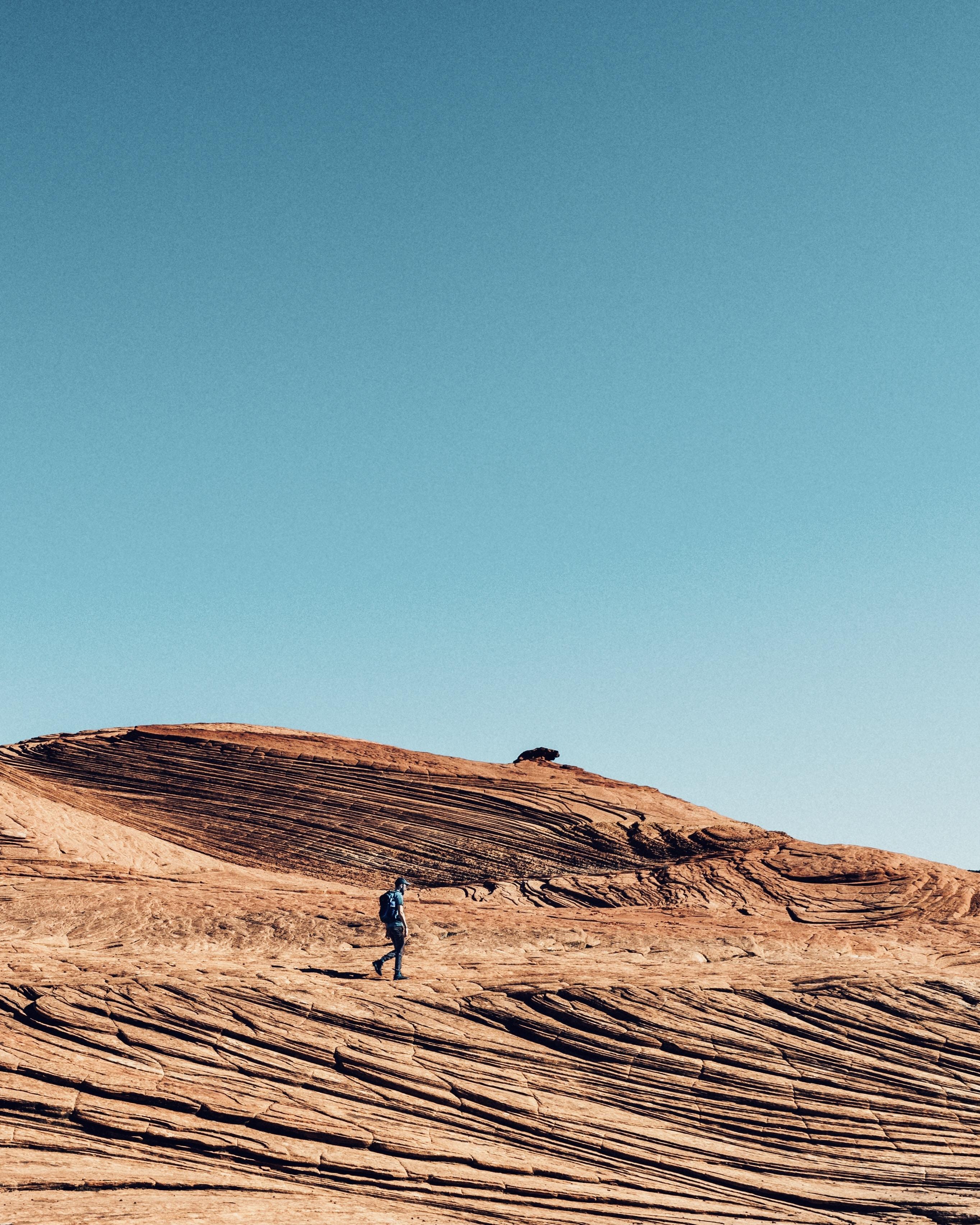 man walking on sand dune during daytime