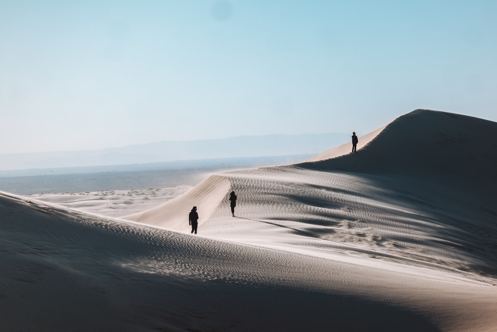 silhouette of three people standing on desert sand during daytime