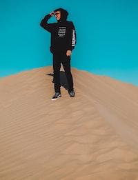 man wearing black pullover hoodie, black pants and black Vans OldSkool sneakers standing on desert sand
