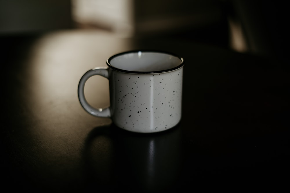 white and black ceramic cup on black surface