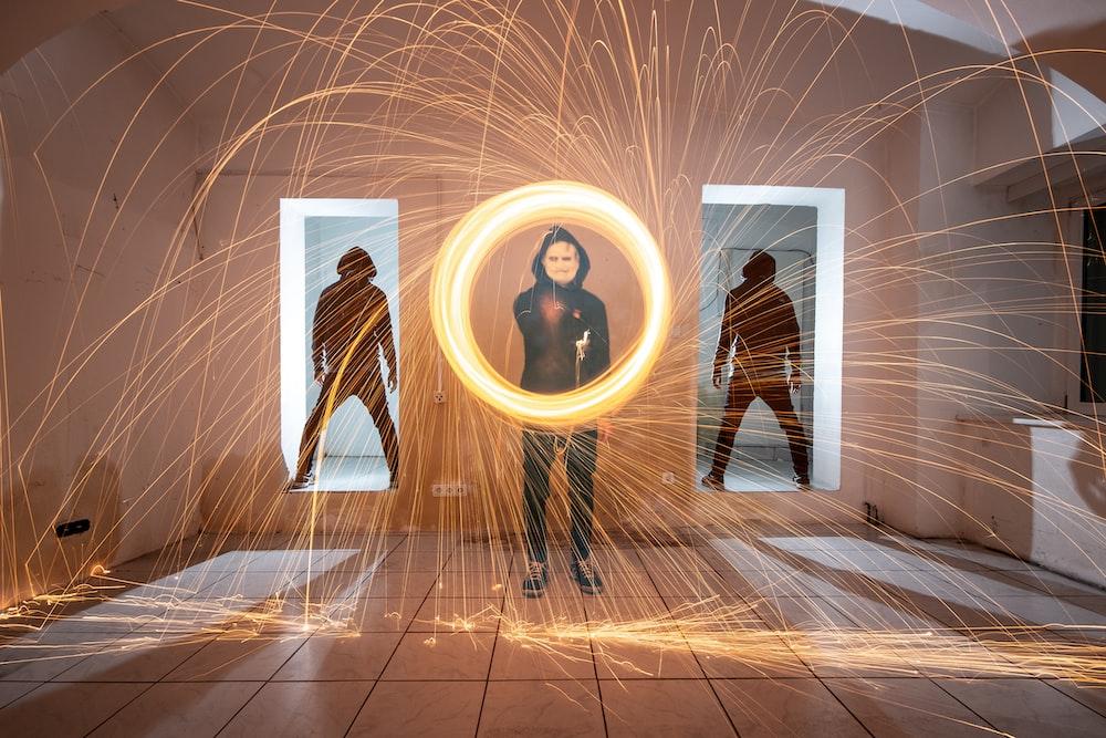 man holding fire sparks inside room