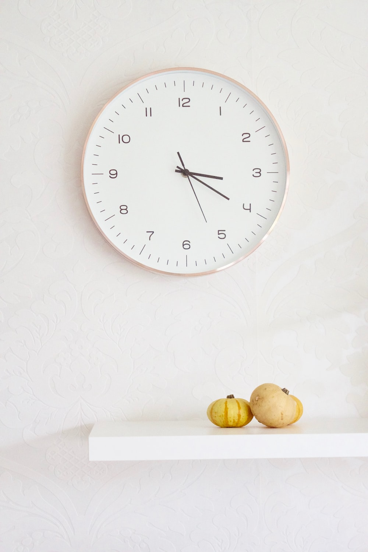 two pumpkins on table below wall clock
