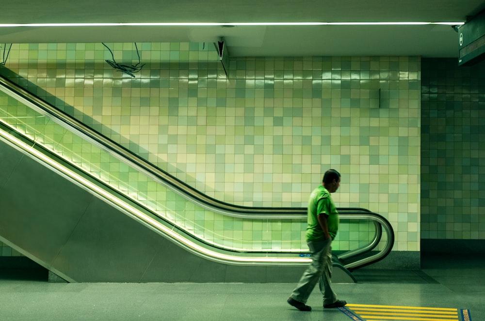 man walking beside escalator