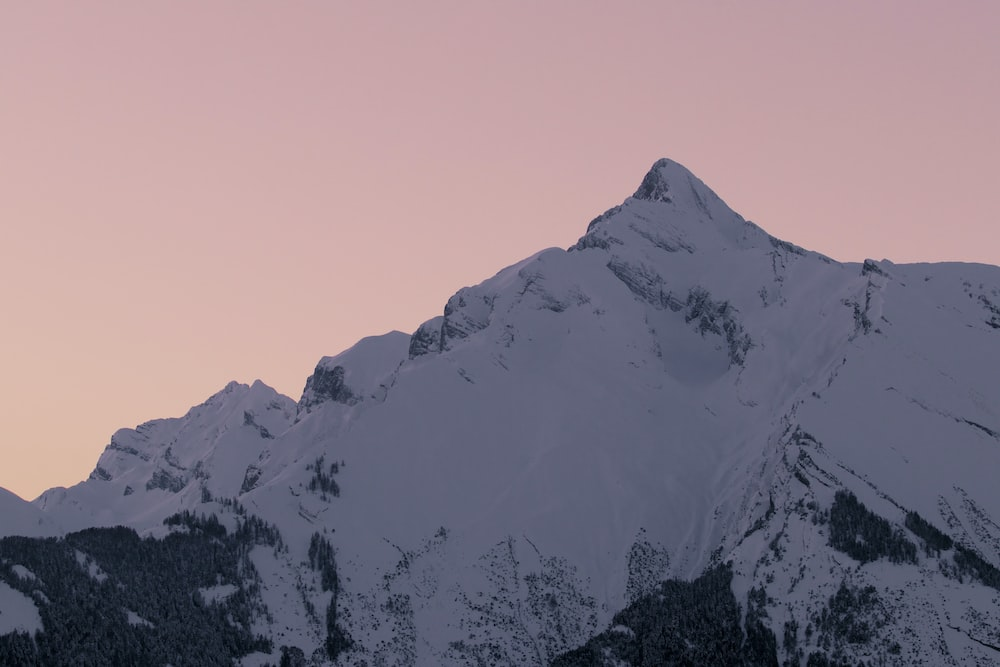 snow covered mountain during sunset