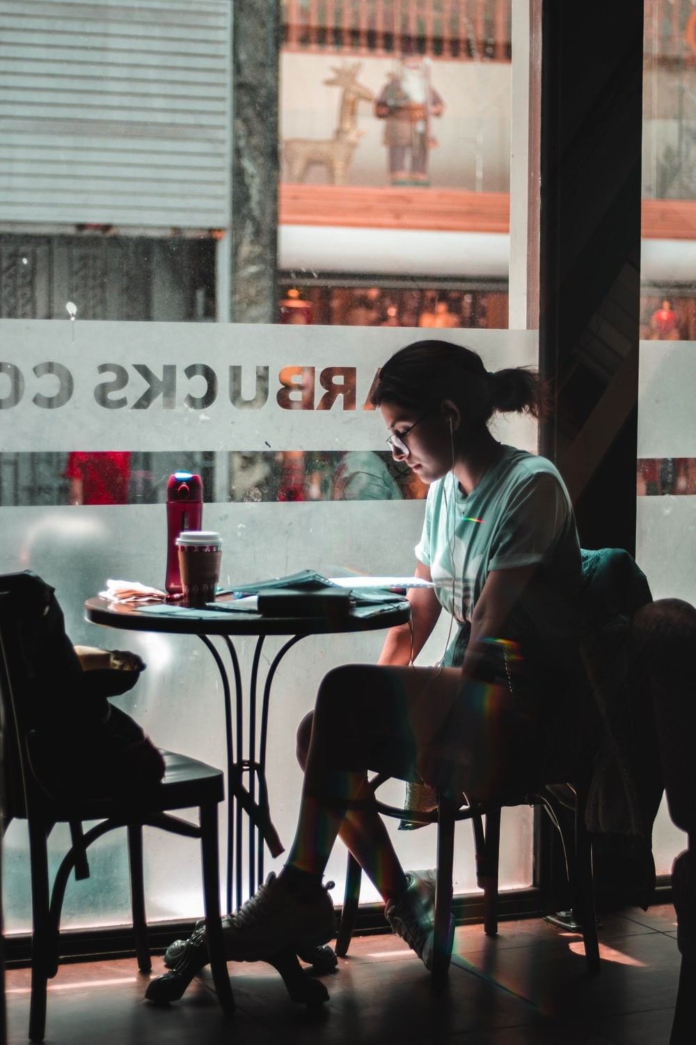 woman sitting alone by the glass window at Starbucks Cafe
