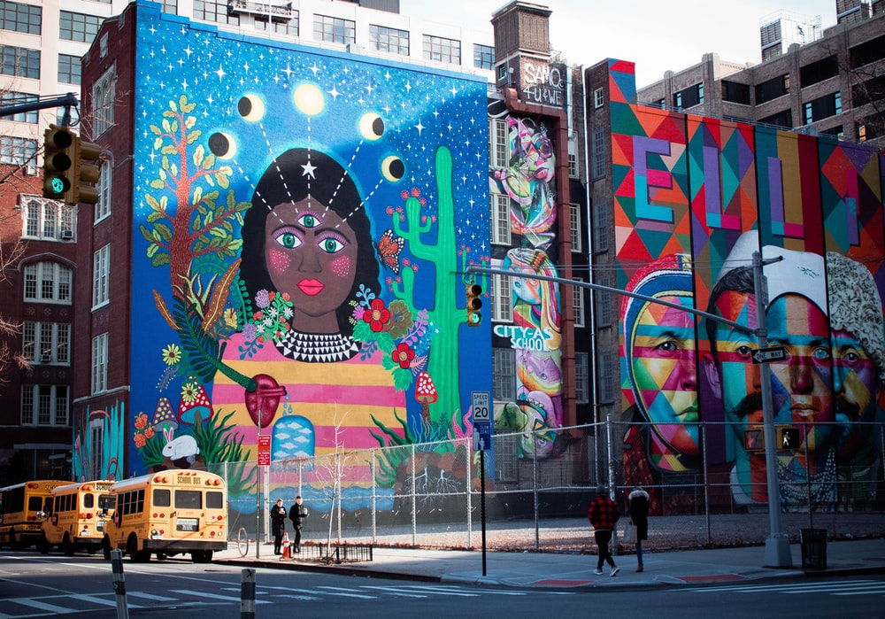people walks beside multicolored building