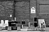 assorted furnitures left beside building with no dumping sign