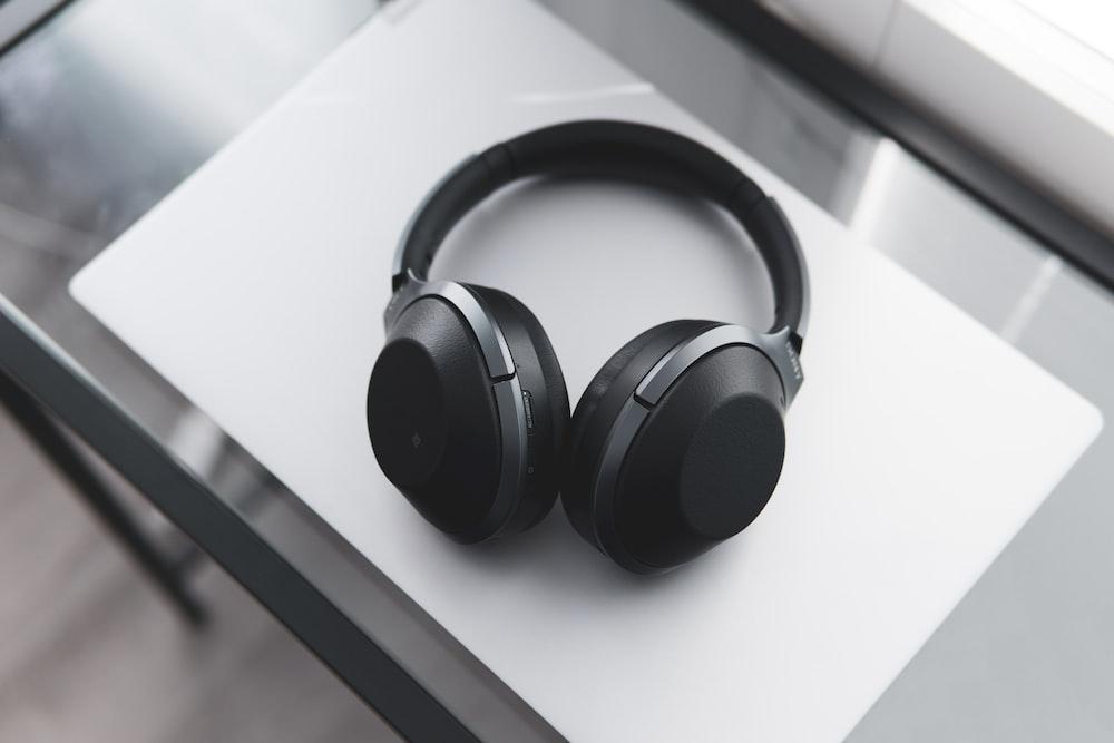 gray and black wireless headphones on desk