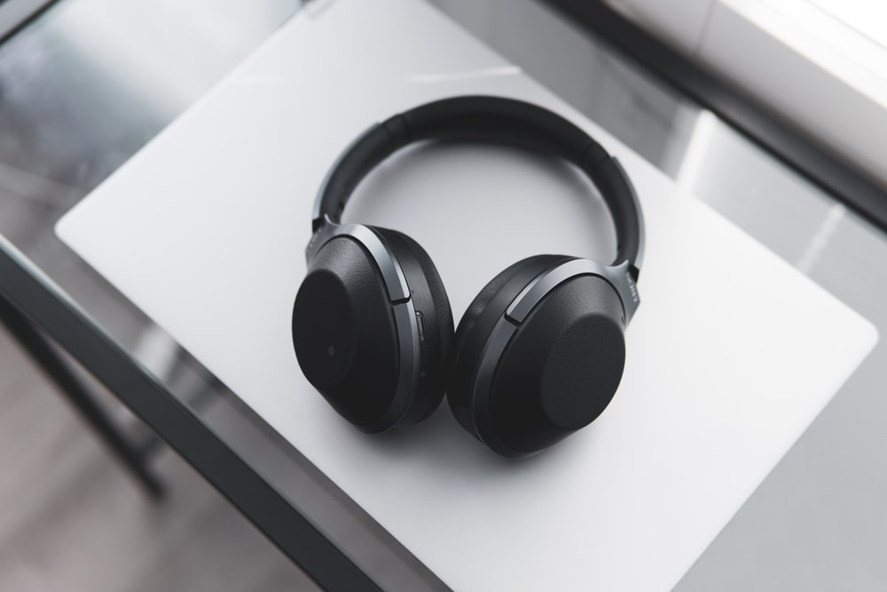 gray and black wireless headphones on desk