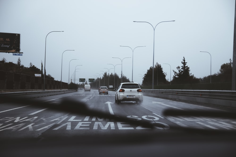 cars on road under white sky
