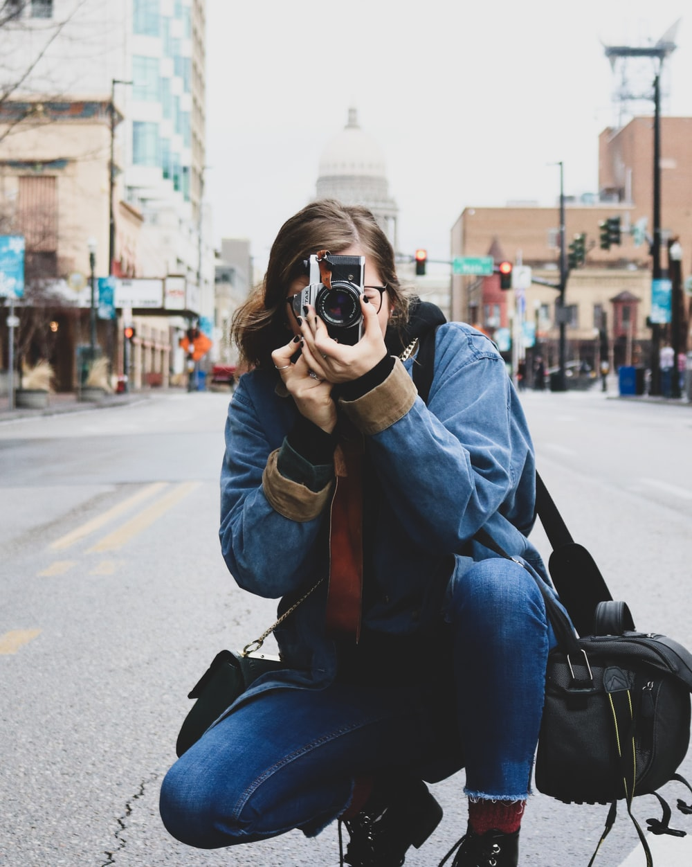 woman in blue denim jeans taking picture on road