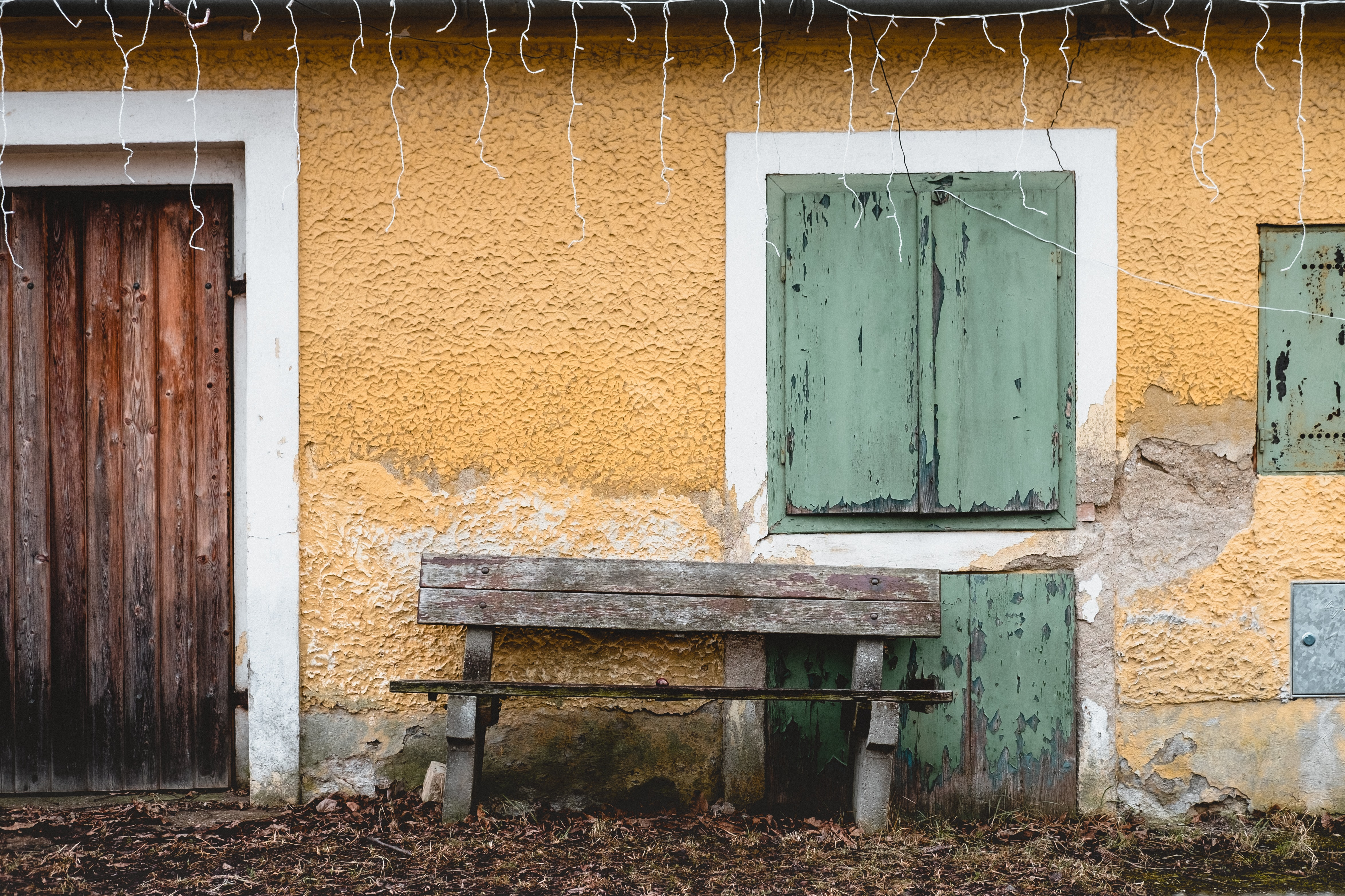 grey wooden empty bench outside yellow concrete house