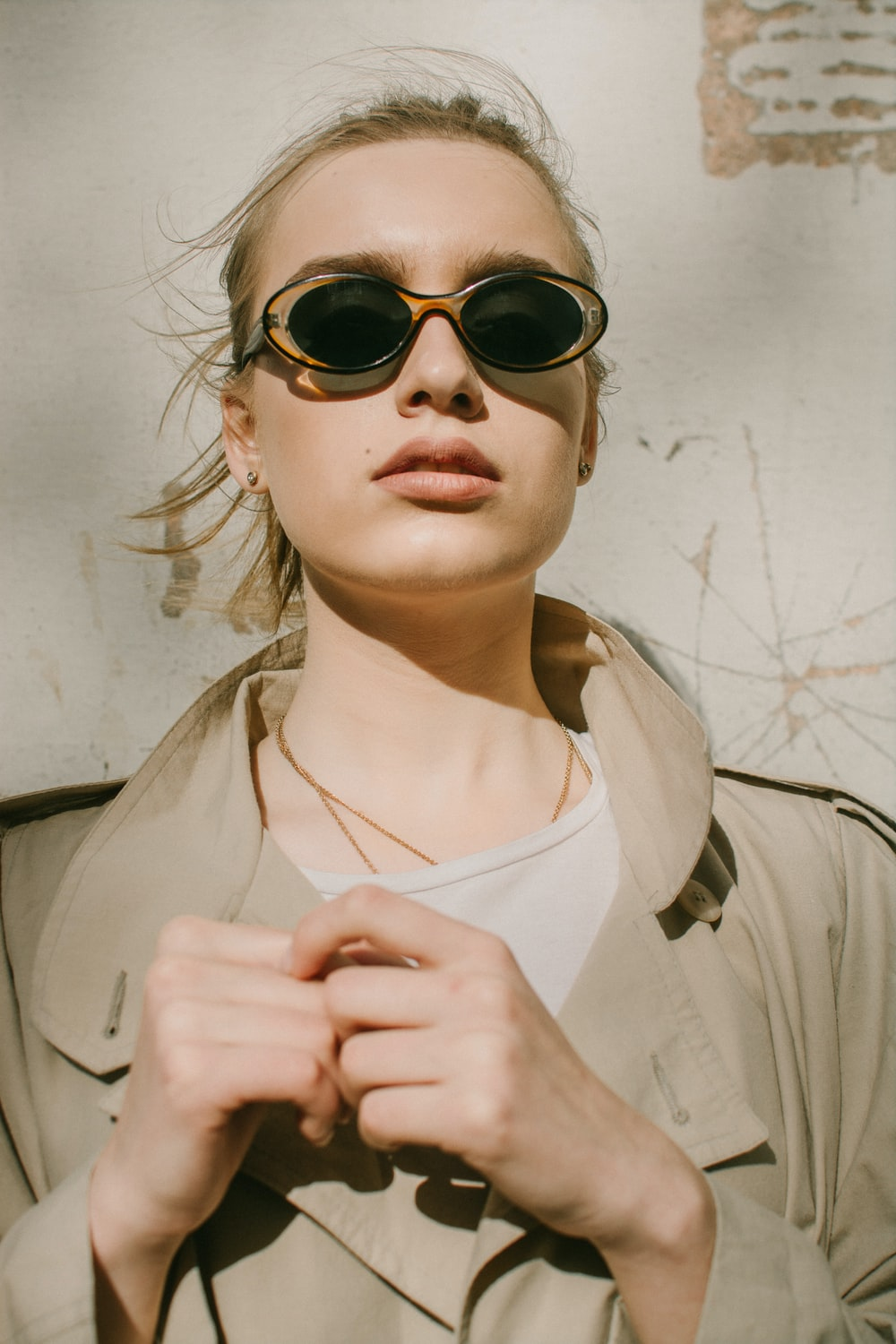 woman in brown coat wearing sunglasses