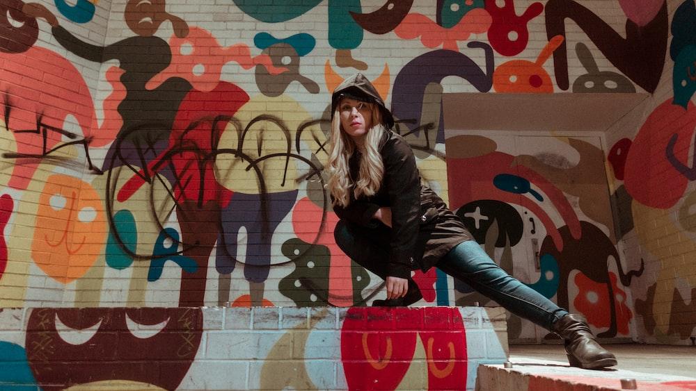 woman in black hoodie sitting near wall art