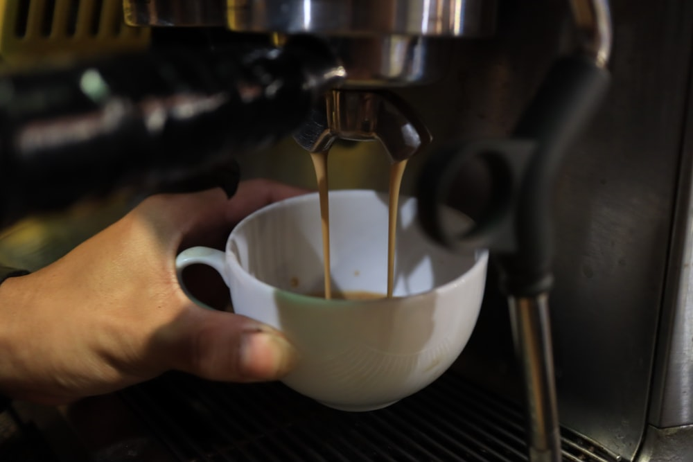 person pouring brown liquid on white teacup