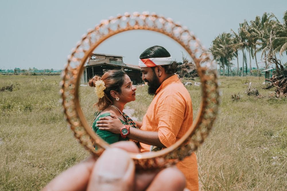 man in orange top facing woman in green dress