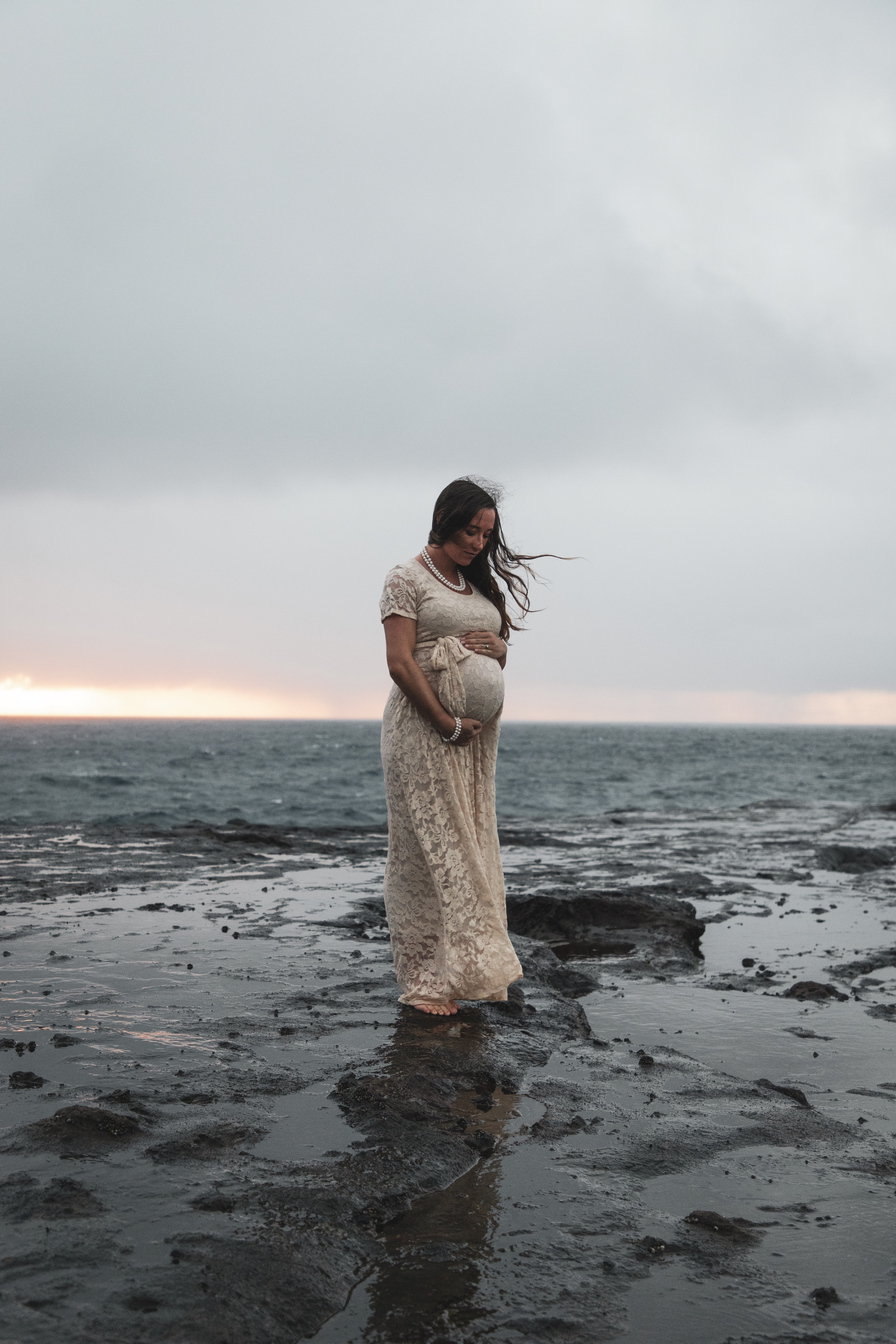 woman standing rock under gray sky