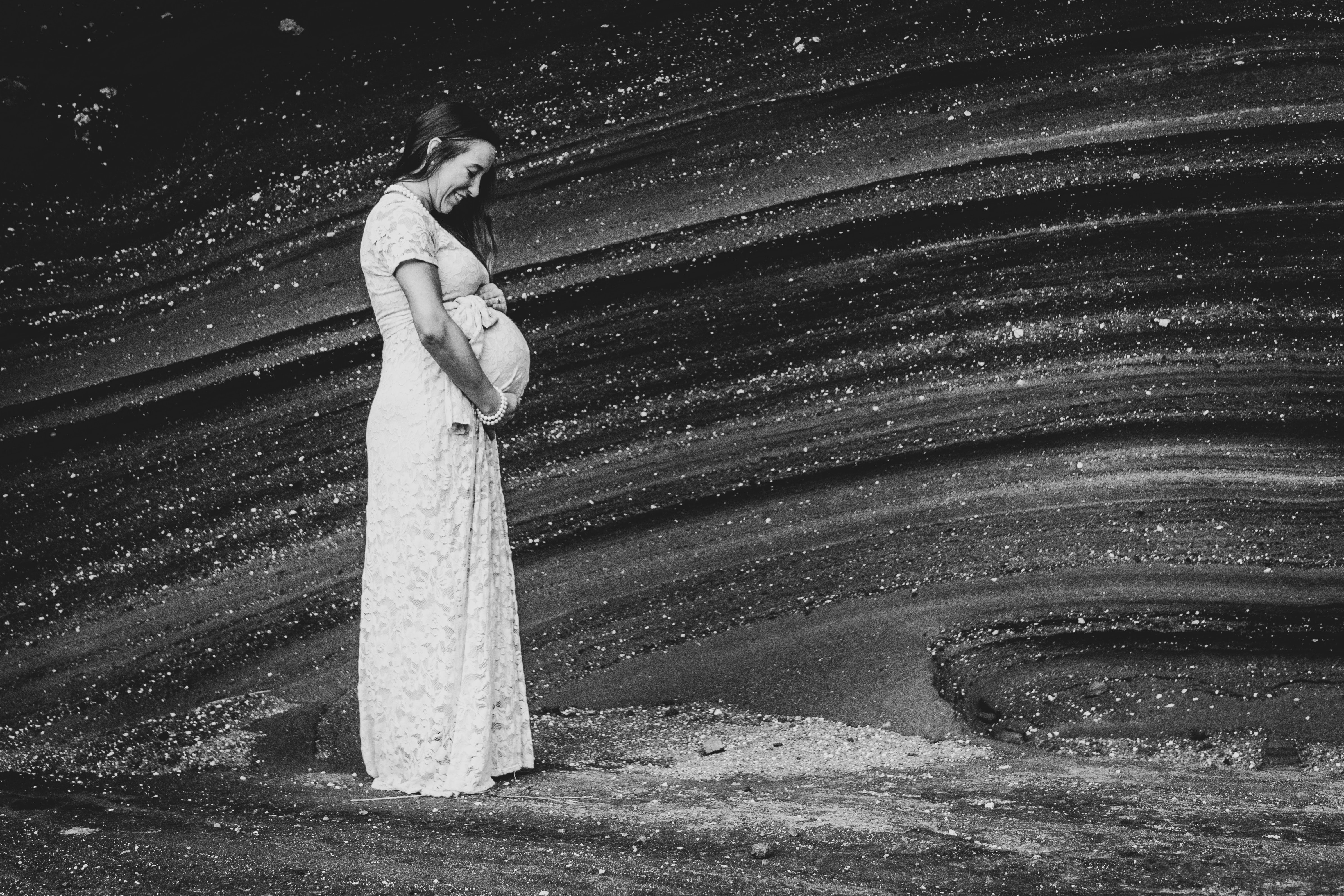 pregnant woman in white dress holding her tummy