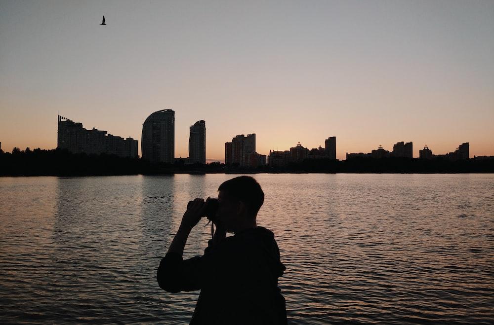 silhouette of person using binoculars