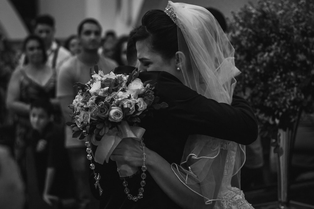 grayscale photo of man and woman hugging