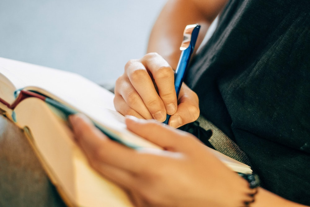 shallow focus photo of person writing