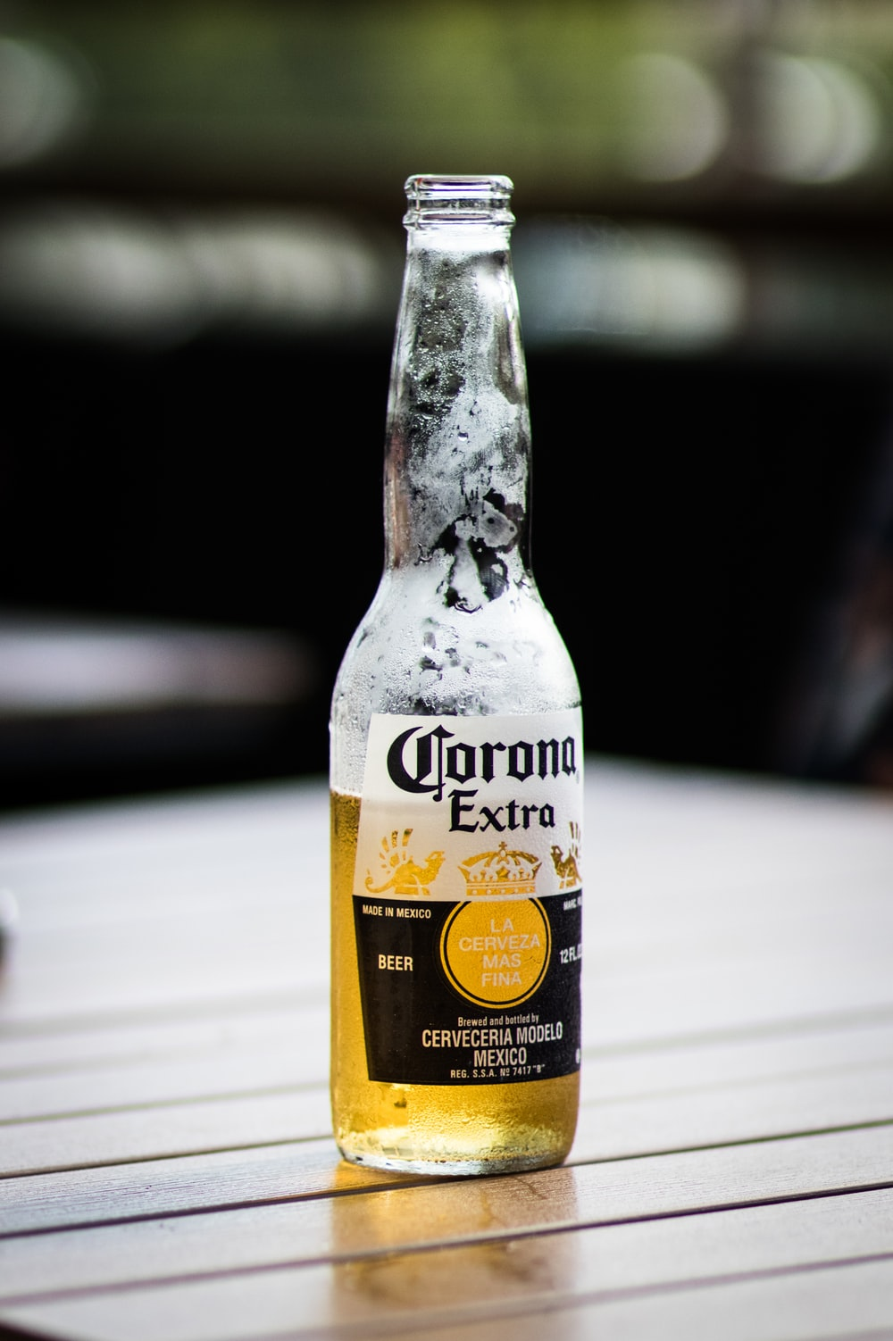 Corona Extra beer bottle on brown wooden surface during daytime