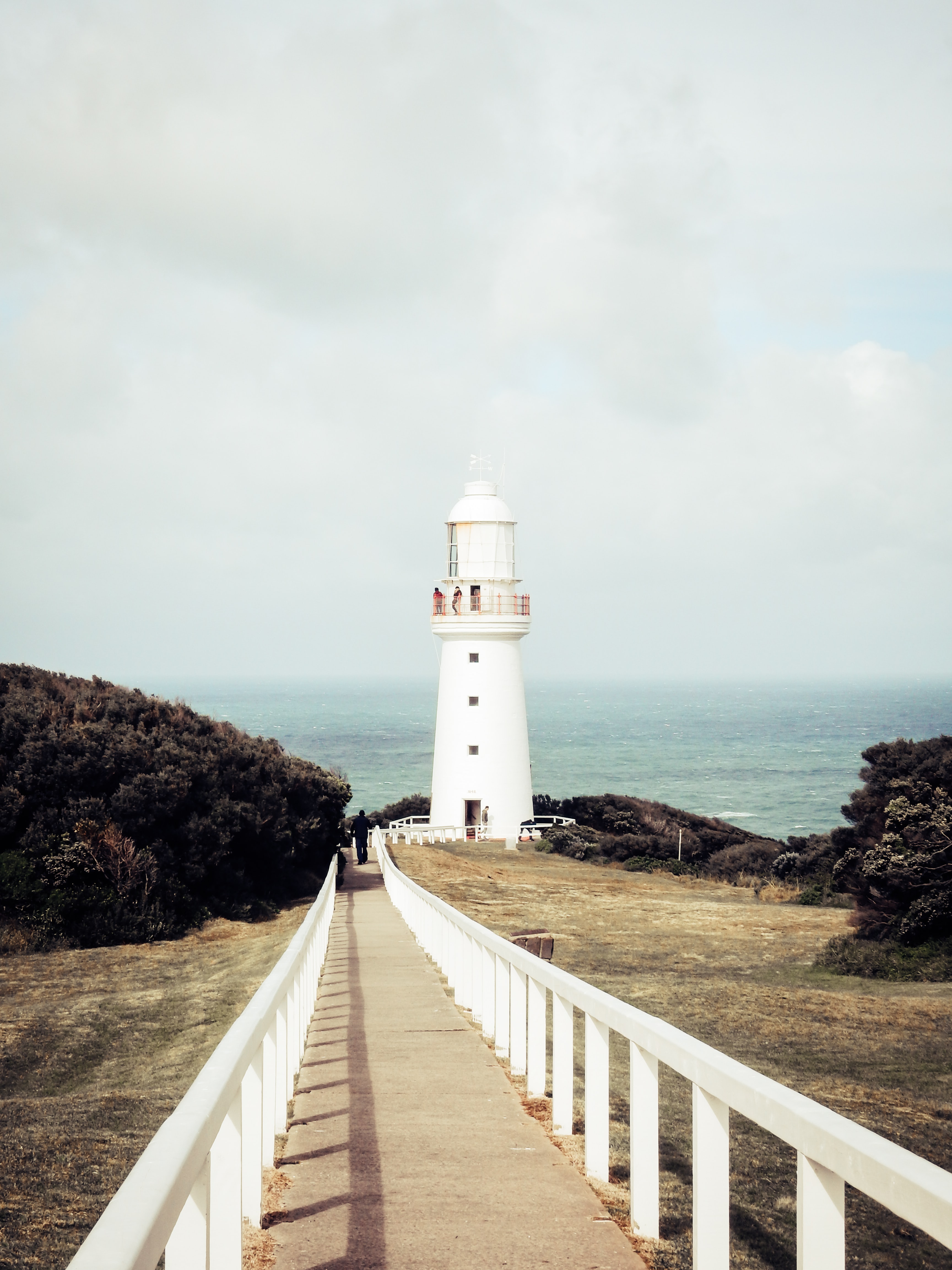 white lighthouse under cloudy sky