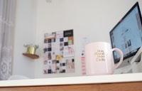 white ceramic mug near flat screen monitor