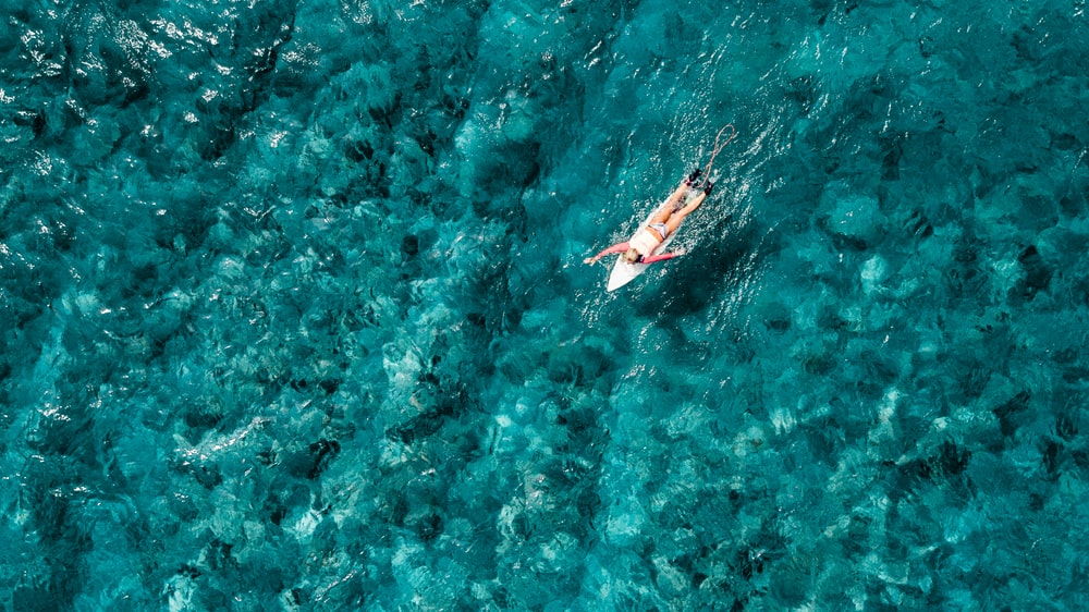 bird's eye view of person surfing on body of water