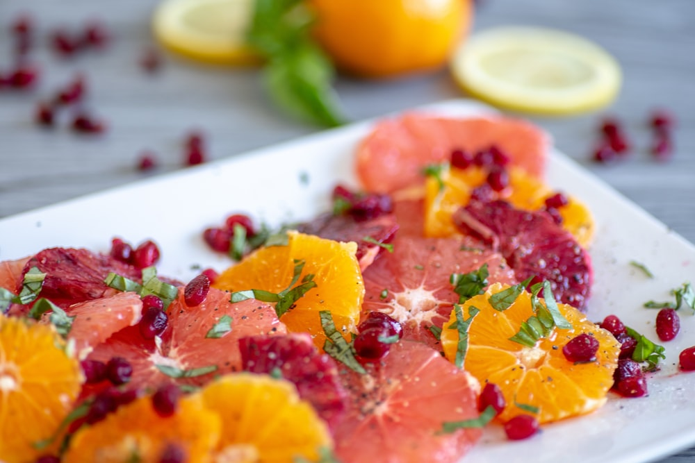 shallow focus photo of sliced fruits on white ceramic tray