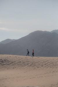 two women walking on dessert during daytime
