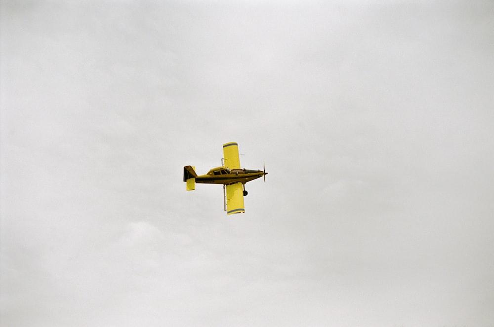 yellow bi-plane flying under white clouds