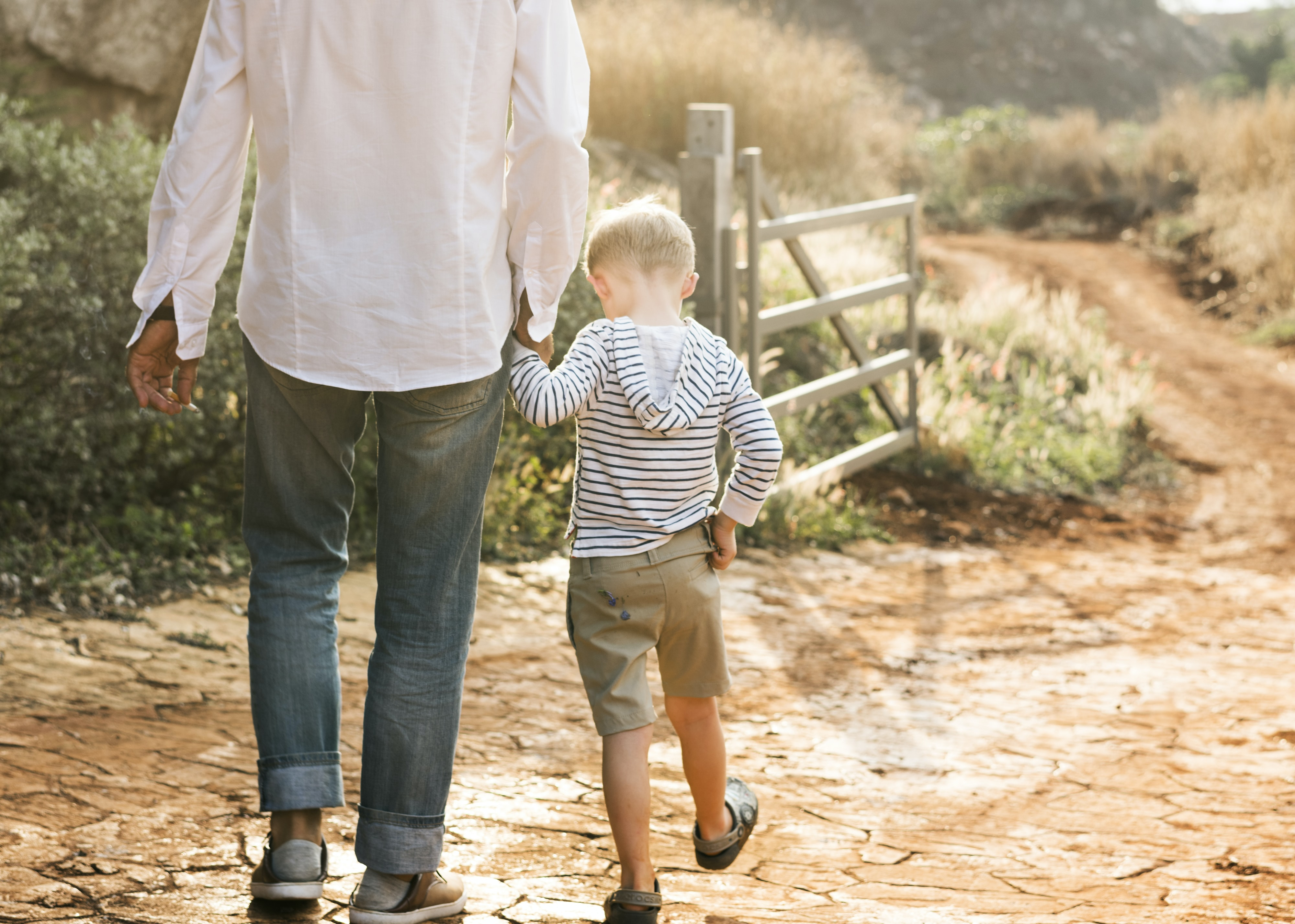 man holding hands with boy while walking during daytime