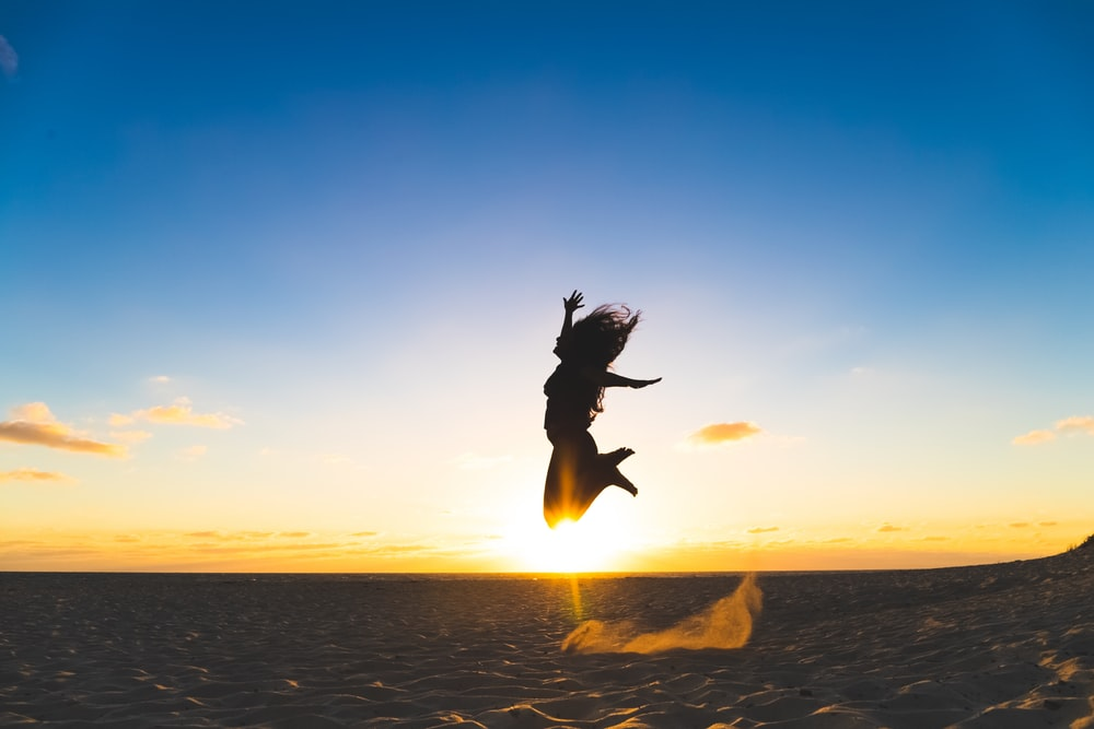 woman leaping at sand during sunset