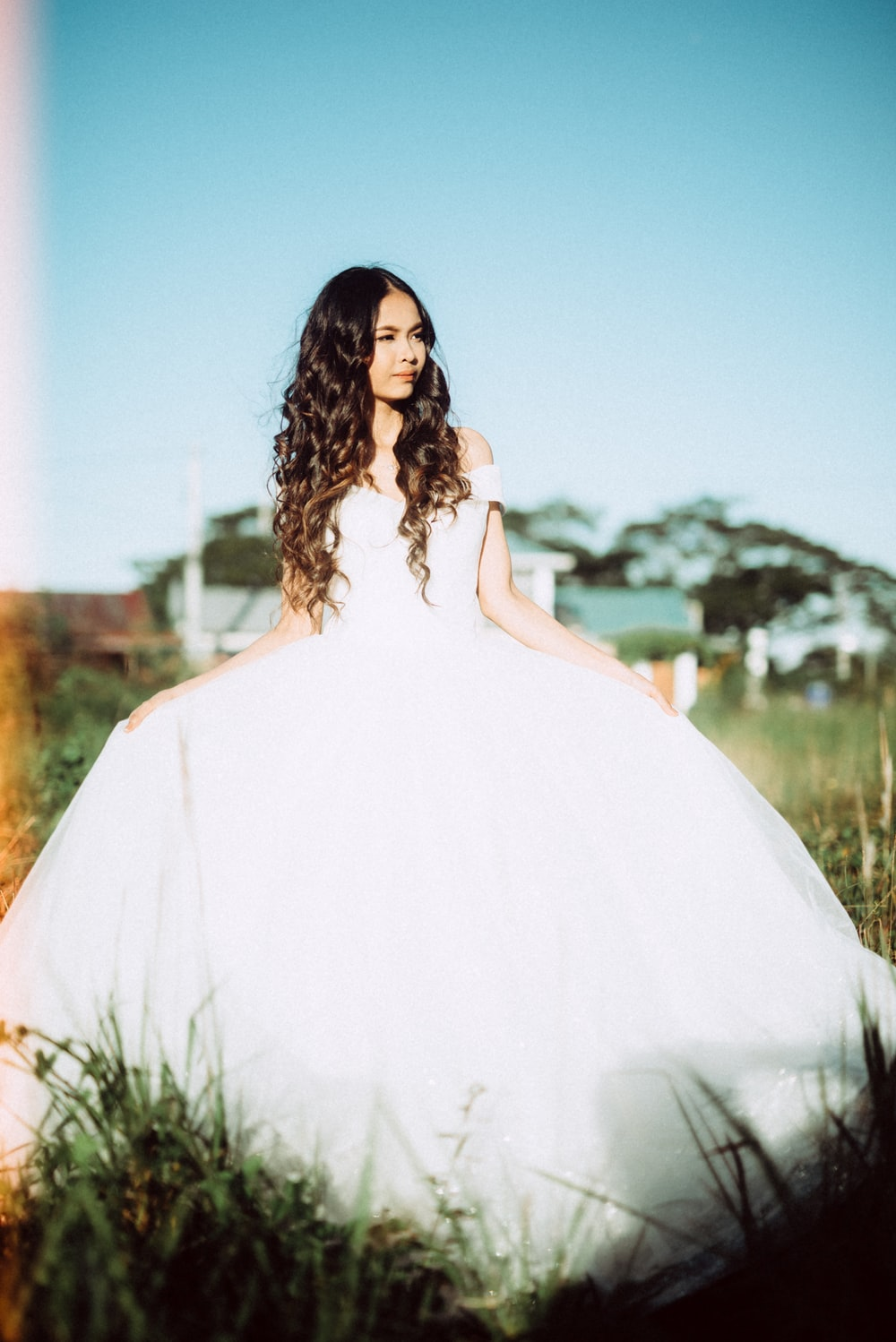 woman in white dress standing on grass field