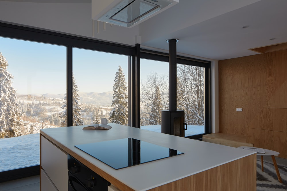 white and brown wooden table beside window