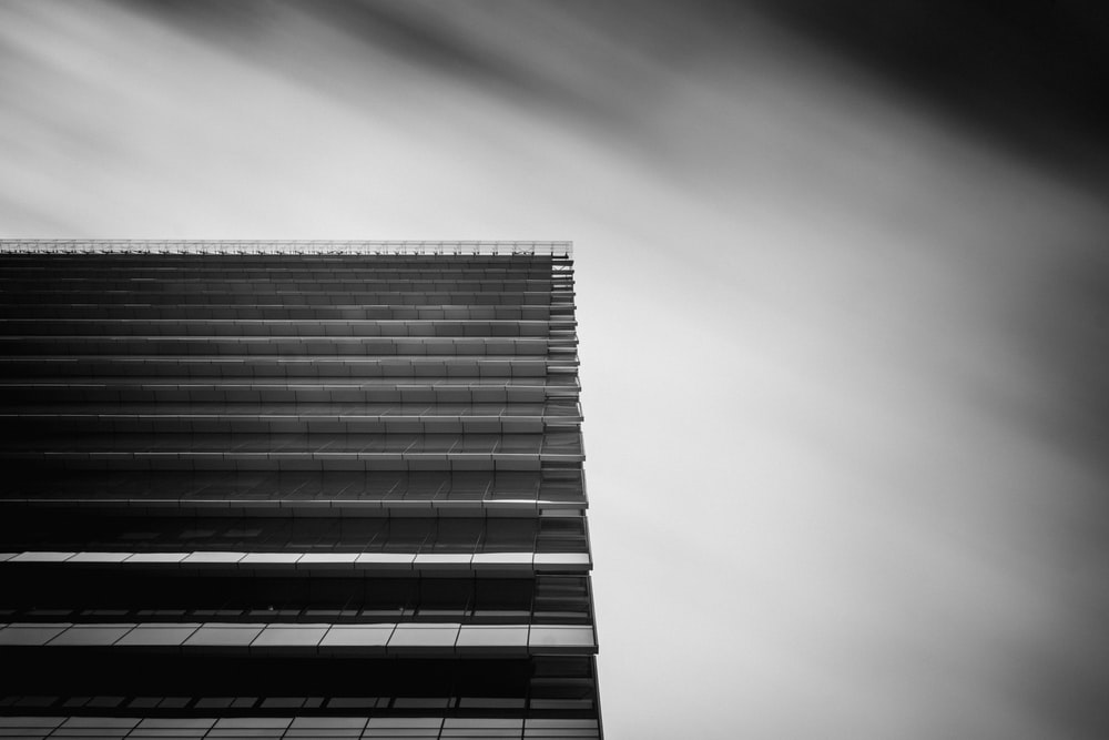 low-angle and grayscale photography of curtain wall building