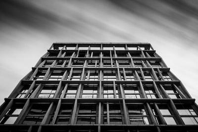 grayscale photography of concrete building noir teams background