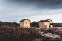 two beige wooden barn houses on field