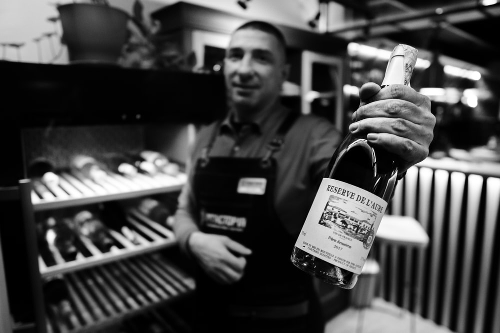 man holding wine bottle beside refrigerator