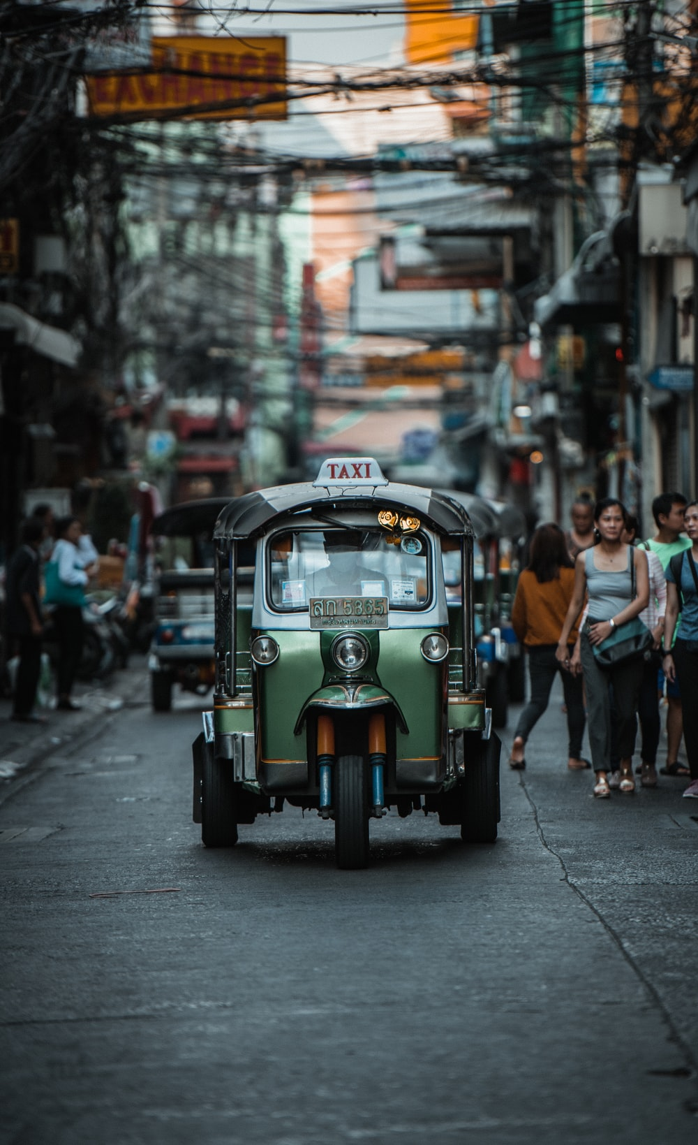 green auto rickshaw on road in between buildings with people walking around during daytime