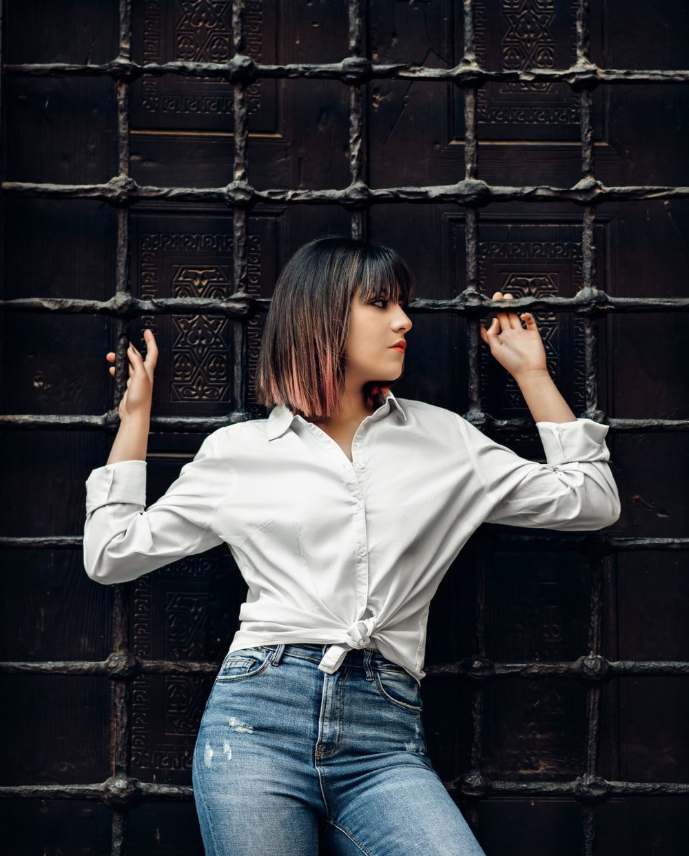 woman in white dress shirt leaning and holding on metal mesh wall