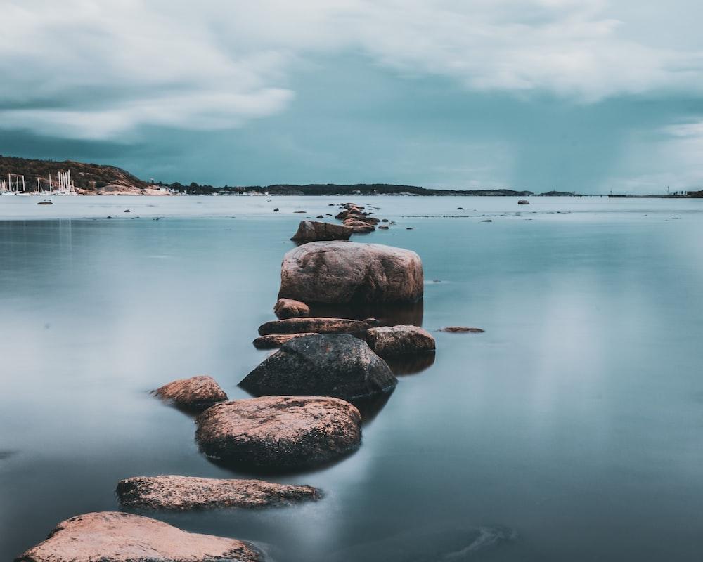 brown rock pathway between calm lake
